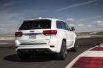 Picture of a driving 2016 Jeep Grand Cherokee SRT 4WD in Bright White Clear Coat from a rear right perspective