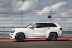 Picture of a driving 2016 Jeep Grand Cherokee SRT 4WD in Bright White Clear Coat from a side perspective
