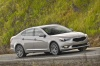 Driving 2016 Kia Cadenza in Silky Silver Metallic from a front right three-quarter view