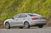 Driving 2016 Kia Cadenza in Silky Silver Metallic from a rear left three-quarter view