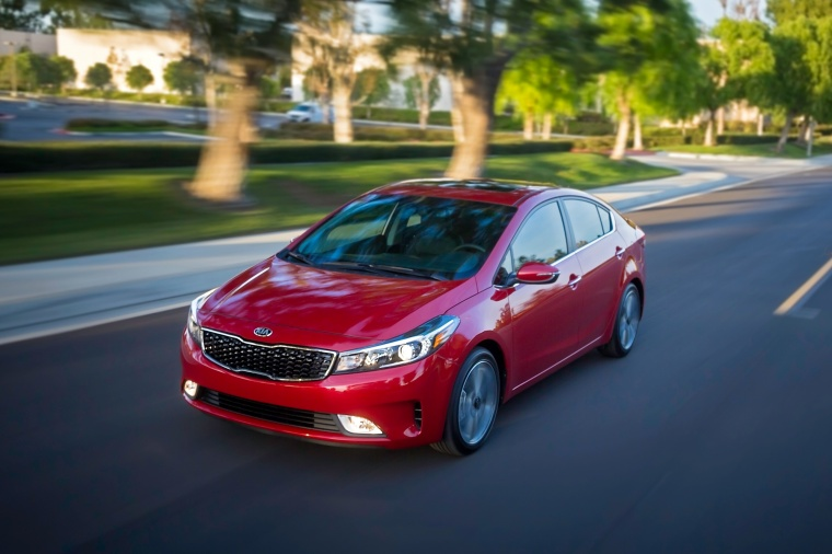 Driving 2018 Kia Forte Sedan in Currant Red from a front left view
