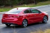 Driving 2018 Kia Forte Sedan in Currant Red from a rear right three-quarter view