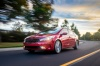 Driving 2018 Kia Forte Sedan in Currant Red from a front left three-quarter view