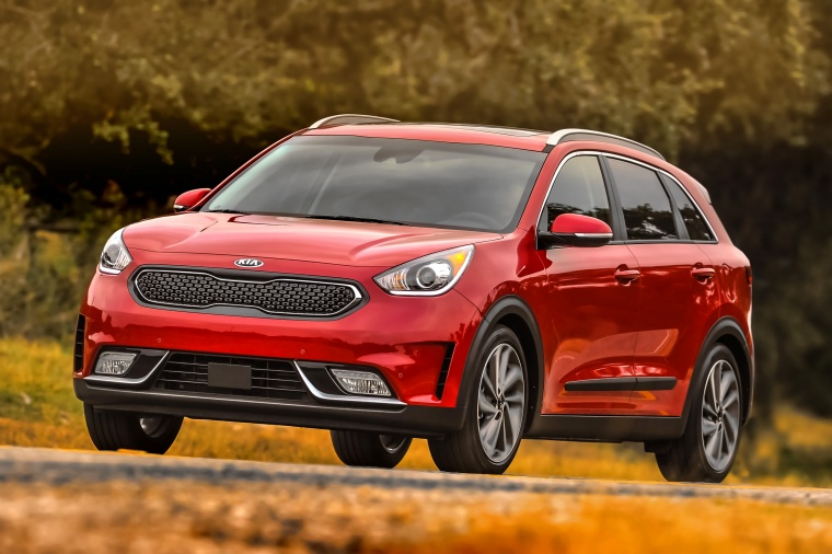 Picture of a driving 2018 Kia Niro Touring Hybrid in Crimson Red from a front left three-quarter perspective