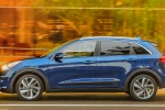 Picture of a driving 2018 Kia Niro Touring Hybrid in Deep Cerulean from a side perspective