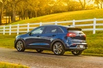 Picture of a driving 2018 Kia Niro Touring Hybrid in Deep Cerulean from a rear left three-quarter perspective