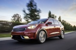 Picture of a driving 2018 Kia Niro Hybrid in Crimson Red from a front left three-quarter perspective