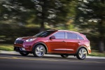 Picture of a driving 2018 Kia Niro Hybrid in Crimson Red from a side perspective