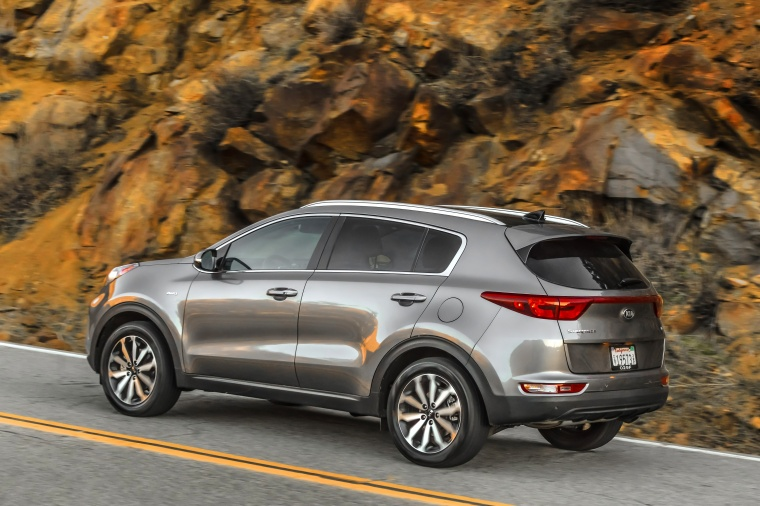 Driving 2018 Kia Sportage EX in Mineral Silver from a rear left three-quarter view