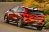 Driving 2018 Kia Sportage SX Turbo in Hyper Red from a rear left three-quarter view