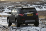 Picture of a driving 2018 Land Rover Discovery Sport HSE Luxury from a rear left perspective