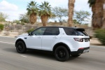 Picture of a driving 2018 Land Rover Discovery Sport HSE Luxury in Fuji White from a rear left three-quarter perspective