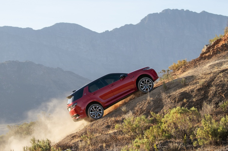 Picture of a driving 2020 Land Rover Discovery Sport P290 HSE R-Dynamic in Firenze Red Metallic from a right side perspective