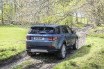 Picture of a driving 2020 Land Rover Discovery Sport P250 S in Byron Blue Metallic from a rear right perspective
