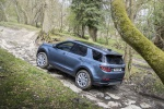 Picture of a driving 2020 Land Rover Discovery Sport P250 S in Byron Blue Metallic from a rear left three-quarter top perspective