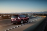 Picture of a driving 2020 Lexus GX460 in Claret Mica from a rear right three-quarter perspective
