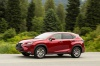 Driving 2019 Lexus NX300h in Matador Red Mica from a side view