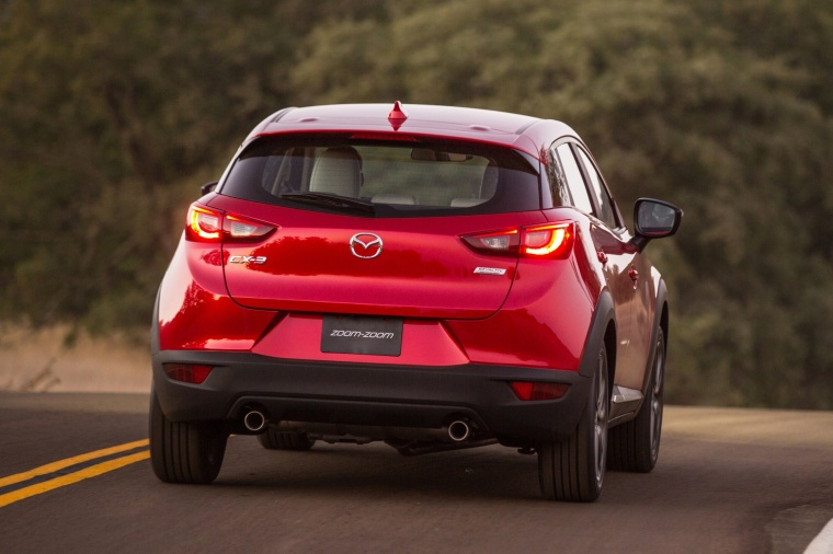 Driving 2017 Mazda CX-3 in Soul Red Metallic from a rear view