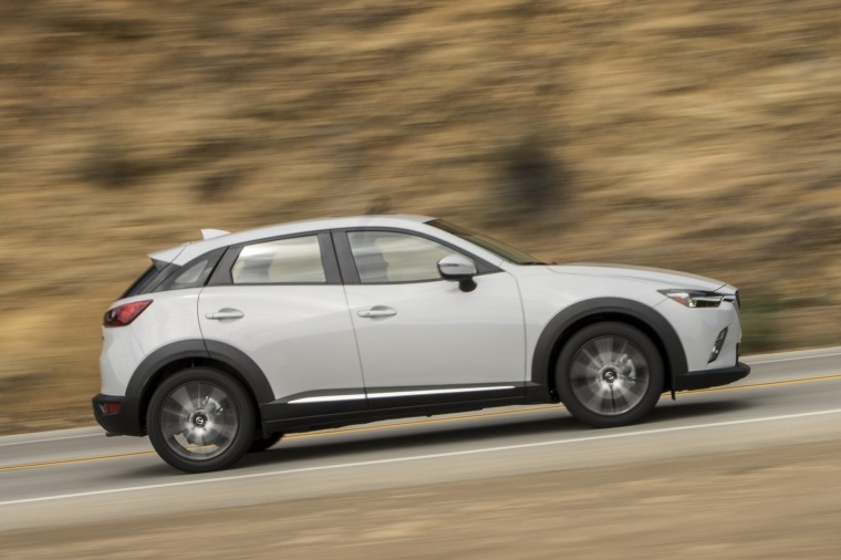 Driving 2017 Mazda CX-3 AWD in Crystal White Pearl Mica from a side view