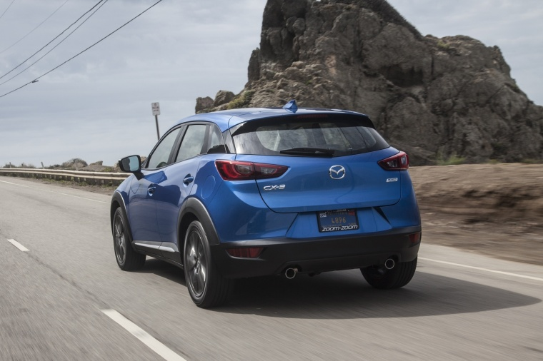 Driving 2017 Mazda CX-3 in Dynamic Blue Mica from a rear left view