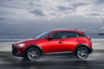 Picture of a driving 2018 Mazda CX-3 in Soul Red Metallic from a side perspective