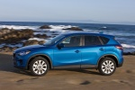 Picture of a driving 2014 Mazda CX-5 in Sky Blue Mica from a left side perspective