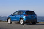Picture of a driving 2014 Mazda CX-5 in Sky Blue Mica from a rear left three-quarter perspective