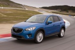 Picture of a driving 2014 Mazda CX-5 in Sky Blue Mica from a front left three-quarter perspective