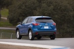 Picture of a driving 2014 Mazda CX-5 in Sky Blue Mica from a rear left perspective