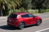Driving 2017 Mazda CX-5 Grand Touring AWD in Soul Red Crystal Metallic from a rear right three-quarter view