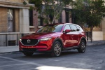 Picture of a driving 2019 Mazda CX-5 Grand Touring AWD in Soul Red Crystal Metallic from a front left perspective