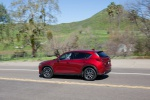 Picture of a driving 2019 Mazda CX-5 Grand Touring AWD in Soul Red Crystal Metallic from a rear left three-quarter perspective