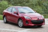 2013 Mazda 3i Sedan in Velocity Red Mica from a front right view