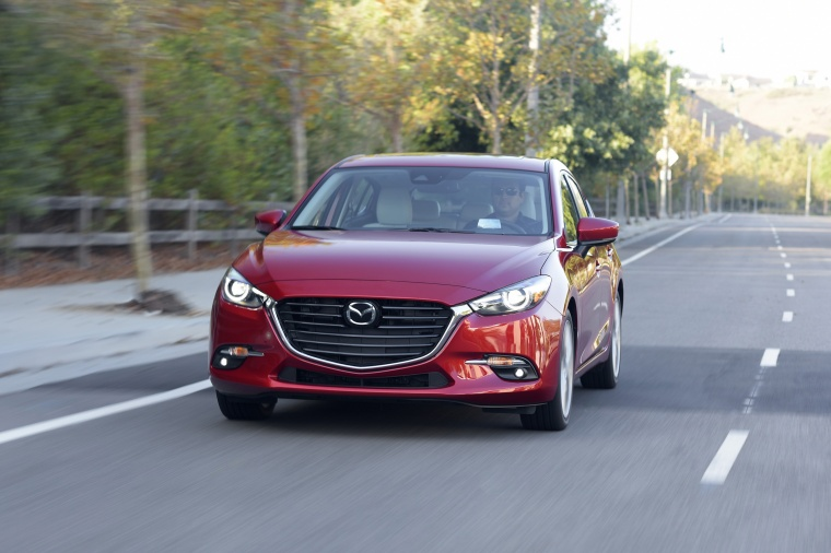 Driving 2018 Mazda Mazda3 Grand Touring 5-Door Hatchback in Soul Red Metallic from a frontal view