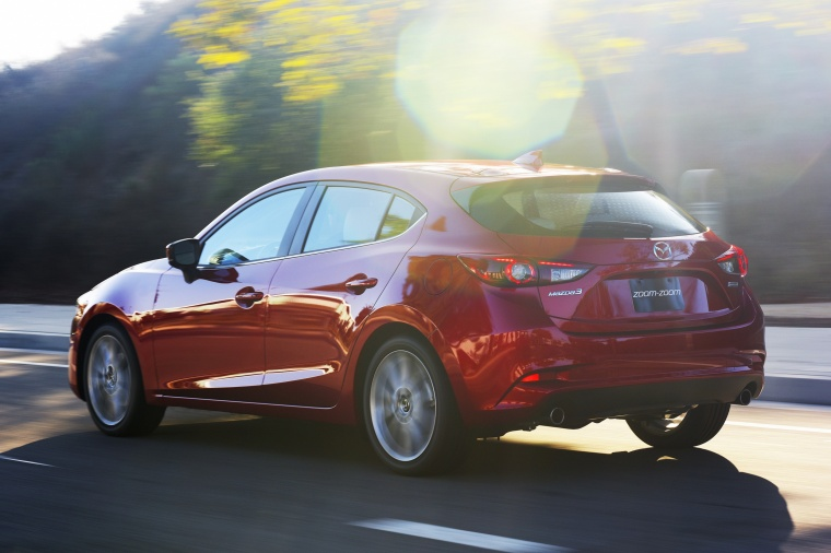 Driving 2018 Mazda Mazda3 Grand Touring 5-Door Hatchback in Soul Red Metallic from a rear left three-quarter view