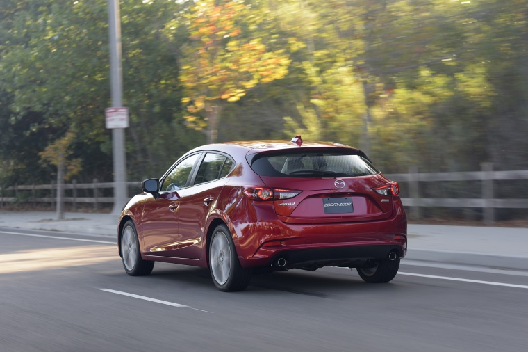 Driving 2018 Mazda Mazda3 Grand Touring 5-Door Hatchback in Soul Red Metallic from a rear left view
