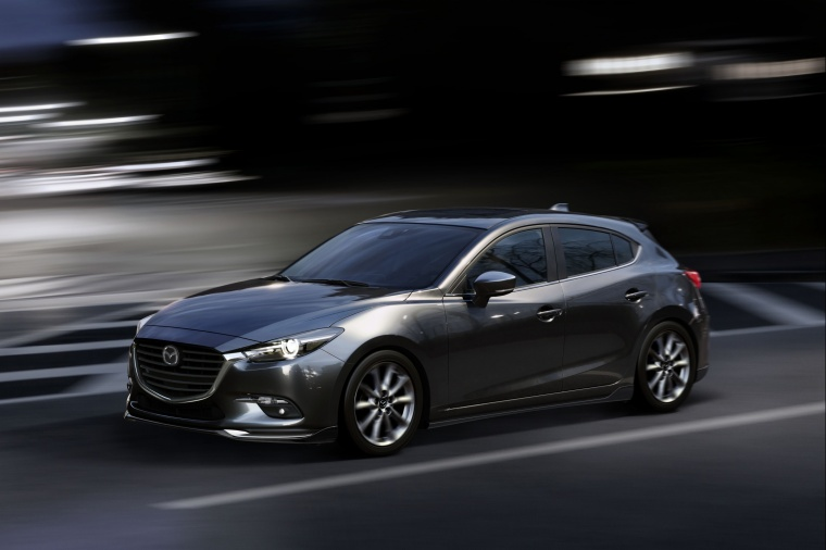Driving 2018 Mazda Mazda3 Grand Touring 5-Door Hatchback in Machine Gray Metallic from a front left three-quarter view