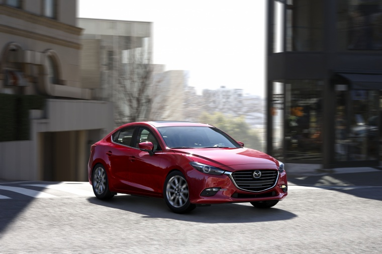Driving 2018 Mazda Mazda3 Grand Touring Sedan in Soul Red Metallic from a front right view