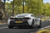 Driving 2017 McLaren 570GT Coupe in Ice Silver from a rear right view