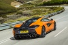 Driving 2017 McLaren 570S Coupe in Ventura Orange from a rear right view