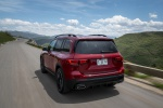 Picture of a driving 2020 Mercedes-Benz GLB 250 in Patagonia Red Metallic from a rear left perspective