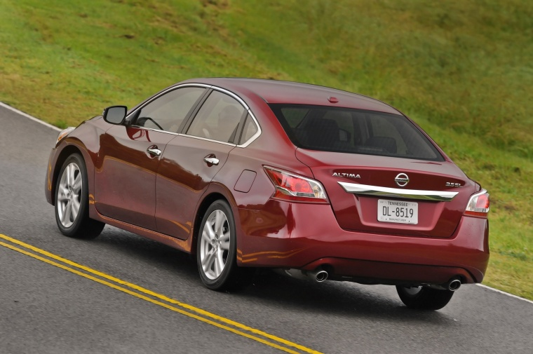 Driving 2015 Nissan Altima Sedan 3.5 SL in Cayenne Red Metallic from a rear left view