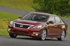 Driving 2015 Nissan Altima Sedan 3.5 SL in Cayenne Red Metallic from a front left three-quarter view