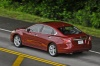 Driving 2015 Nissan Altima Sedan 3.5 SL in Cayenne Red Metallic from a rear left three-quarter view