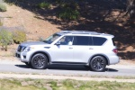 Picture of a driving 2017 Nissan Armada Platinum in Brilliant Silver from a side perspective