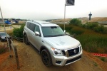 Picture of a driving 2017 Nissan Armada Platinum in Brilliant Silver from a front right perspective