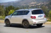 Picture of a driving 2019 Nissan Armada Platinum in Brilliant Silver from a rear left three-quarter perspective