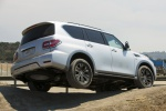 Picture of a driving 2020 Nissan Armada Platinum in Brilliant Silver Metallic from a rear right three-quarter perspective