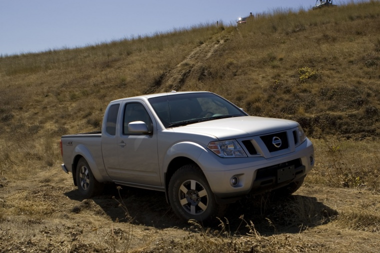 Driving 2010 Nissan Frontier King Cab PRO-4X 4WD in Radiant Silver from a front right three-quarter view