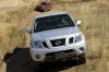 Driving 2010 Nissan Frontier King Cab PRO-4X 4WD in Radiant Silver from a frontal view